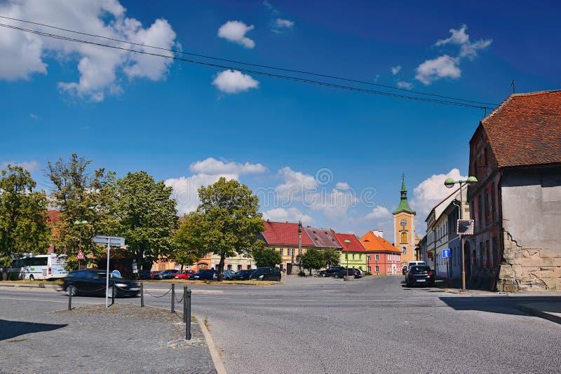 Kravare Machuv kraj, Tjeckien - Juli 14, 2018: genomskärning nära fyrkanten med parkerade bilar, historiska hus och kyrkan royaltyfri foto