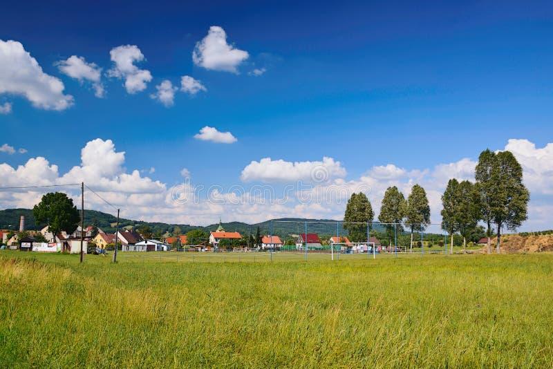 Kravare Machuv kraj, Tjeckien - Juli 14, 2018: tjeckiskt sommarlandskap nära den Kravare byn med ängen, fotbollfält, hou royaltyfri foto