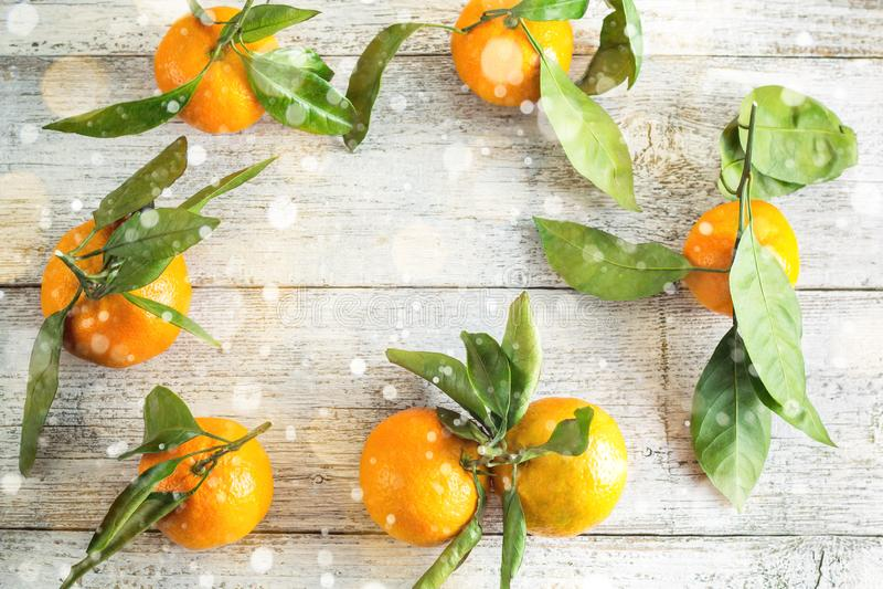 Krawędź pomarańczowych tangeryn z zielonymi liśćmi na białym drewnianym tle Górny widok i miejsce na kopiowanie fotografia royalty free