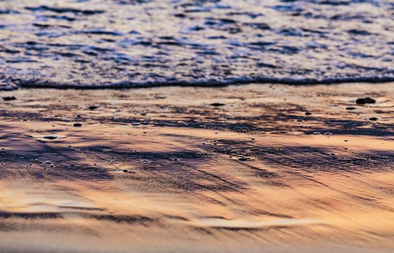 Krawędź wody morskiej przy zachodzie słońca lub wschodzie słońca Tekstura fal i piasku w promieniach zachodzących słońca Kopiuj m zdjęcie stock