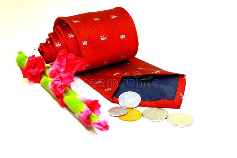 Krawatte, Blume und Münzen im weißen Hintergrund stockbild