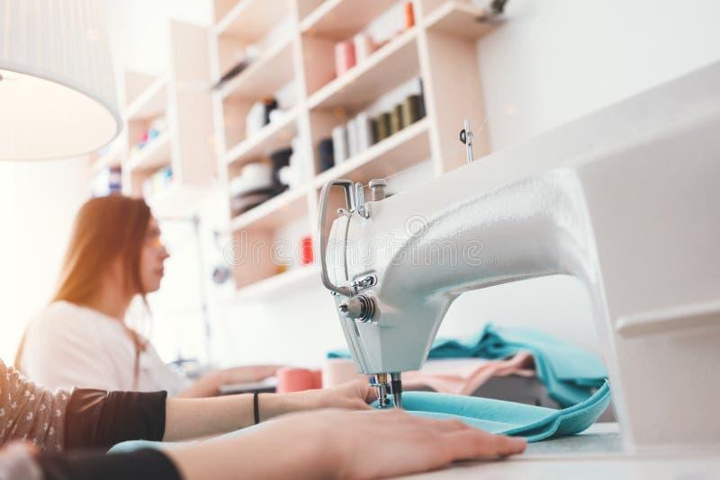 Krawcowej kobieta pracuje na szwalnej maszynie w studiu Dwa szwaczka robi nowemu mody pojęciu odziewa w kreatywnie sala wystawowe obrazy royalty free