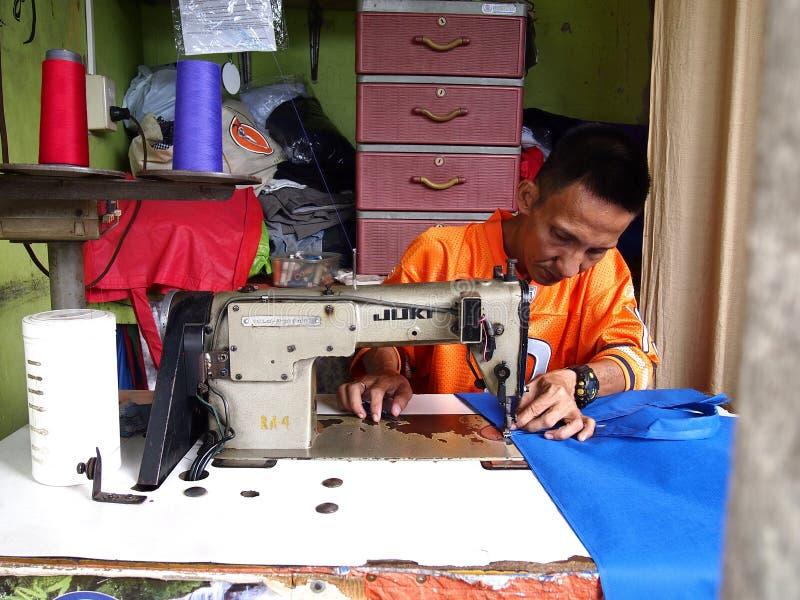 Krawczyna pracuje na sukni z jego szwalną maszyną zdjęcia royalty free