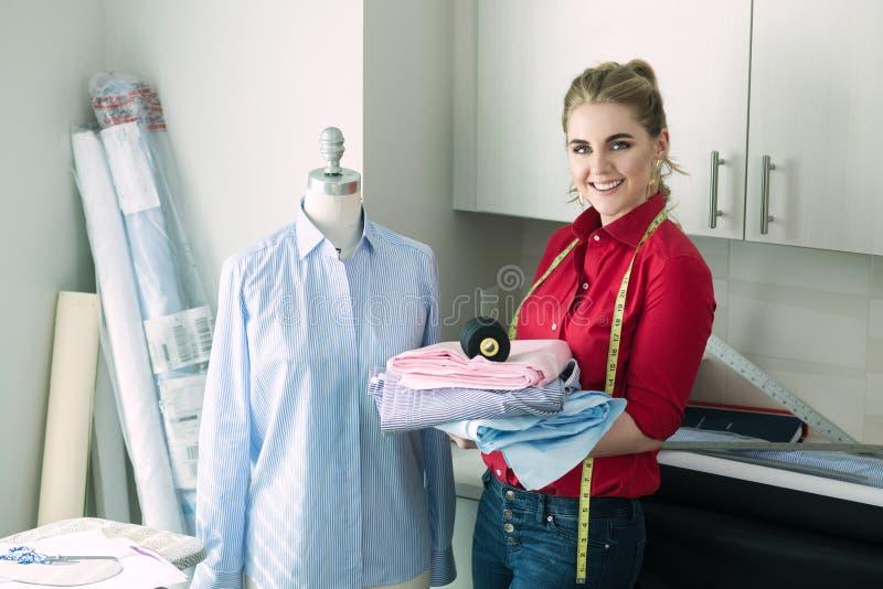 Krawiecka kobieta ono uśmiecha się w atelier projekta pracownianym mieniu szy narzędzia zdjęcia stock