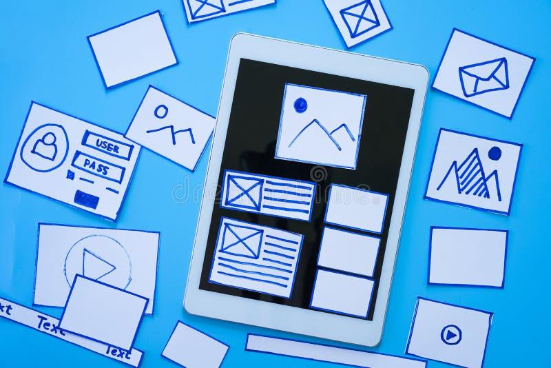 Kreative Designer, die wireframe Skizzenplan-Entwurfsmodell auf Smartphone- oder Tablettenschirm entwerfen lizenzfreie stockbilder