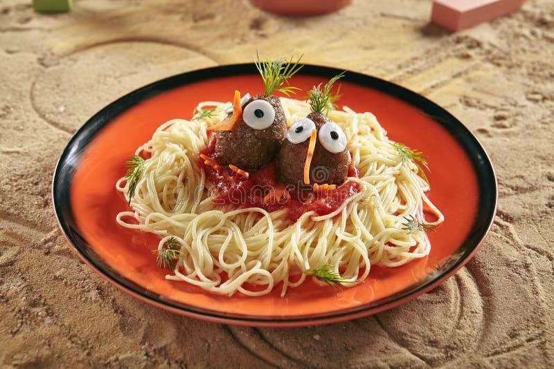 Kreative dienende Kinder Nahrung mit Nudeln, Tomatensauce und Fleisch-Bällen stockfotos