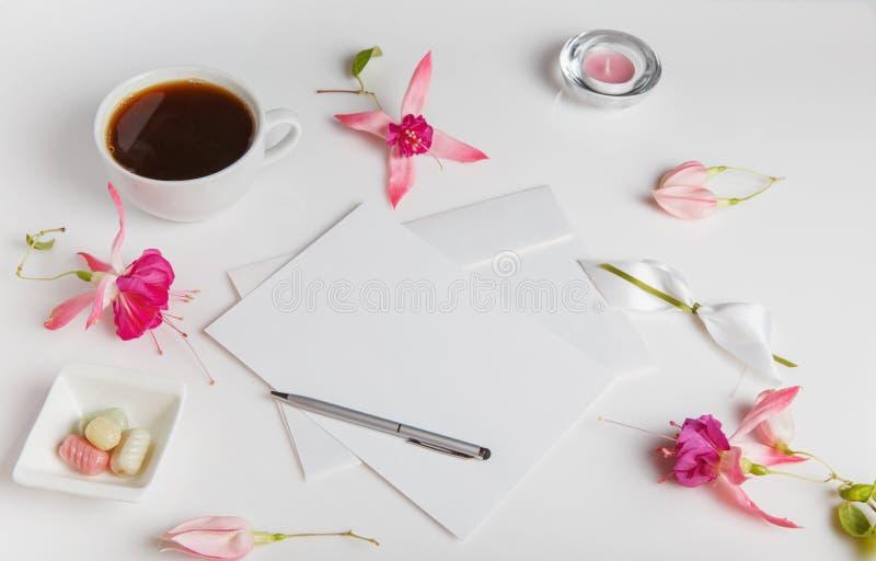 Kreative Ebene legen Foto des Arbeitsplatzschreibtisches mit Smartphone, Kaffee, Bleistift, Blumen mit Kopienraumhintergrund Flac lizenzfreie stockfotos
