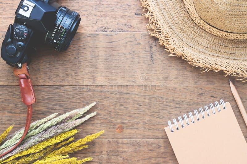 Kreative Ebenenlage des Herbstkonzeptes mit Trockenblumen, Kamera, Strohhut und Notizbuch auf Holz stockfotografie