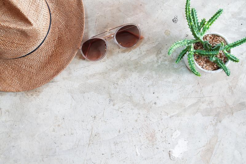Kreative flache Lage des modischen Sonnenbrille-, Strohhut- und Tonwarenkaktus auf konkretem Hintergrund Reiselebensstil stockfotos