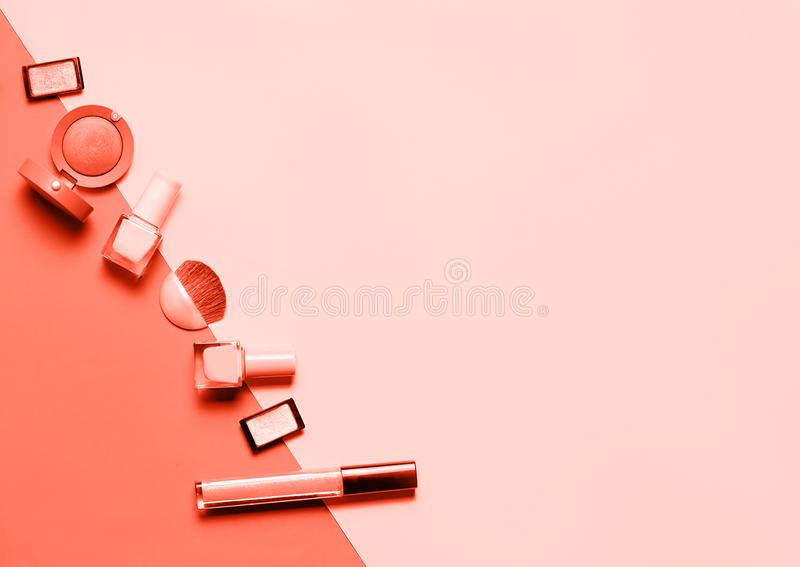 Kreative flache Lage von hellen Nagellacken der Mode und dekorativer von Kosmetik auf gefärbt in der Farbe Jahr 2019 Lebenkoralle stockfotos