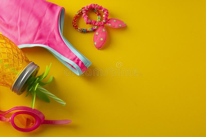 Kreative flache Lage von Strandgegenst?nden Unbedeutendes Artkonzept der Sommerferien Gelber Hintergrund mit Ananasweckglassaft, stockbilder