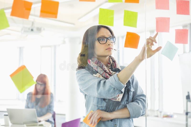 Kreative Geschäftsfrau, die klebrige Anmerkungen auf Glaswand mit dem Kollegen arbeitet im Hintergrund im Büro liest lizenzfreies stockbild