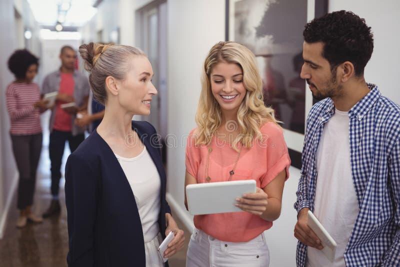 Kreative Geschäftsleute, die über digitaler Tablette im Korridor sich besprechen lizenzfreie stockfotografie