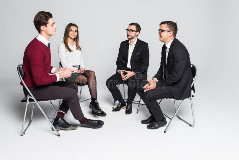 Kreative Geschäftsleute, die im Kreis von den Stühlen lokalisiert auf Weiß sich treffen stockfoto