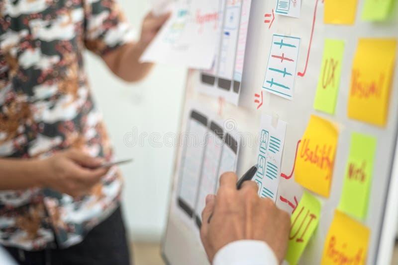 Kreative Gruppe UX-Designers, die über die Planierung des beweglichen Anwendungsprojektes mit klebrigen Anmerkungen arbeitet Benu stockbild