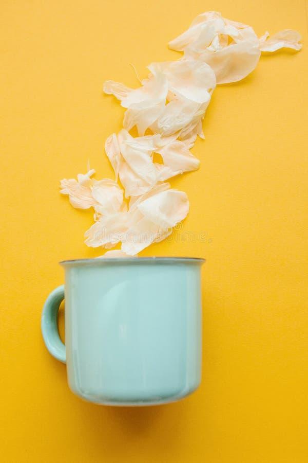 Kreative Idee Ein Becher, von dem weiße Blumenblätter heraus wie Dampf von einem heißen Getränk im Winter flogen lizenzfreies stockbild