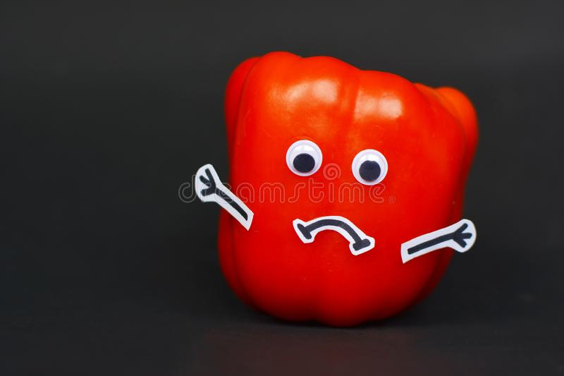 Kreative Nahrungsmittelphotographie des roten reifen Paprikas mit den lustigen Schutzbrillenaugen, Stockhänden und traurigem Mund lizenzfreie stockbilder