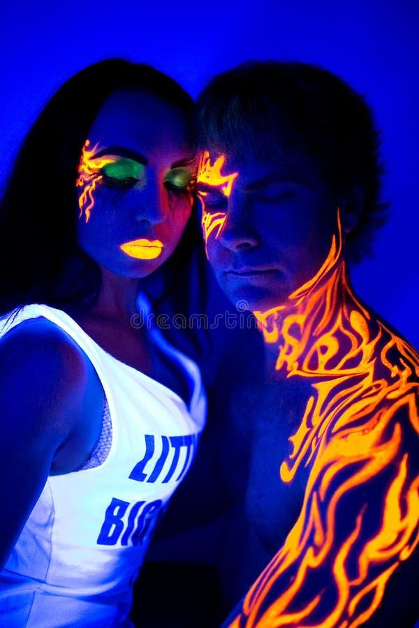 Kreative Neonlichtmann- und -frauenschönheit bilden Körperkunst lizenzfreie stockfotografie