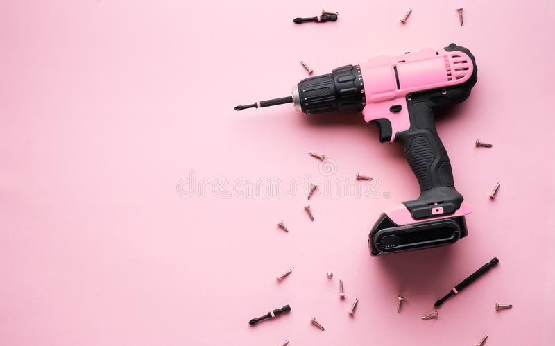 Kreative Provokation: ein rosa Schraubenzieher auf einem rosa Hintergrund und kleinen rosa Schrauben stockfotos
