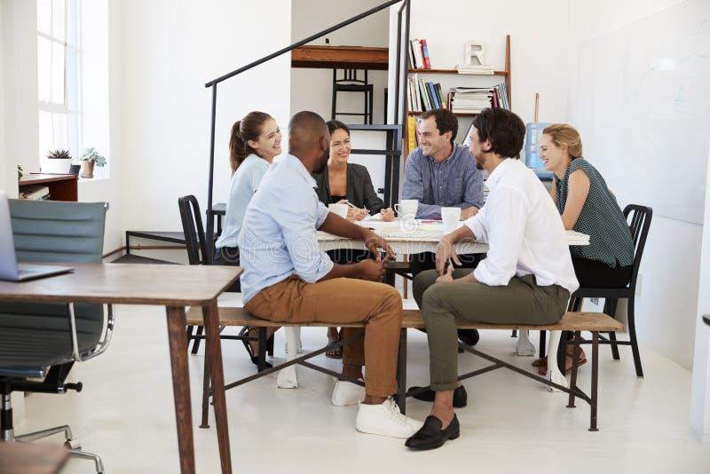 Kreative Teambesprechung um eine Tabelle in einem Büro lizenzfreie stockfotografie