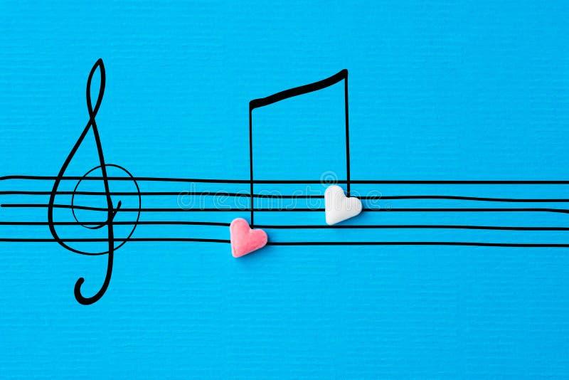Kreative Valentinsgrußgrußkarte Zuckerherz-Formsüßigkeiten übergeben gezogener Gekritzelskizze musikalische Anmerkungen über Pers stockfotografie