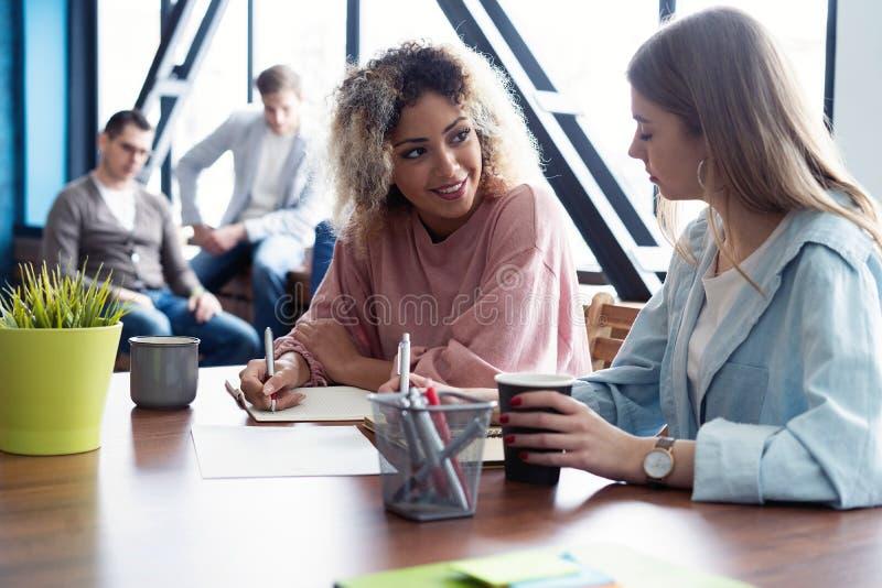 Kreative weibliche Designer, die im Team arbeiten Zwei Geschäftsfrauen, die informelle Sitzung im modernen Büro haben stockbild
