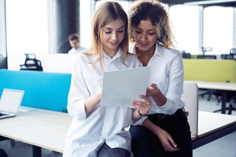 Kreative weibliche Designer, die im Team arbeiten Zwei Gesch?ftsfrauen, die informelle Sitzung im modernen B?ro haben stockfotografie