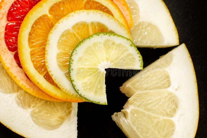 Kreative Zitrusfrüchte schneiden auf einem schwarzen Hintergrund, abstrakt Zitrone, Orange, Kalk, Pampelmuse, Herzchen, Pampelmus lizenzfreies stockbild