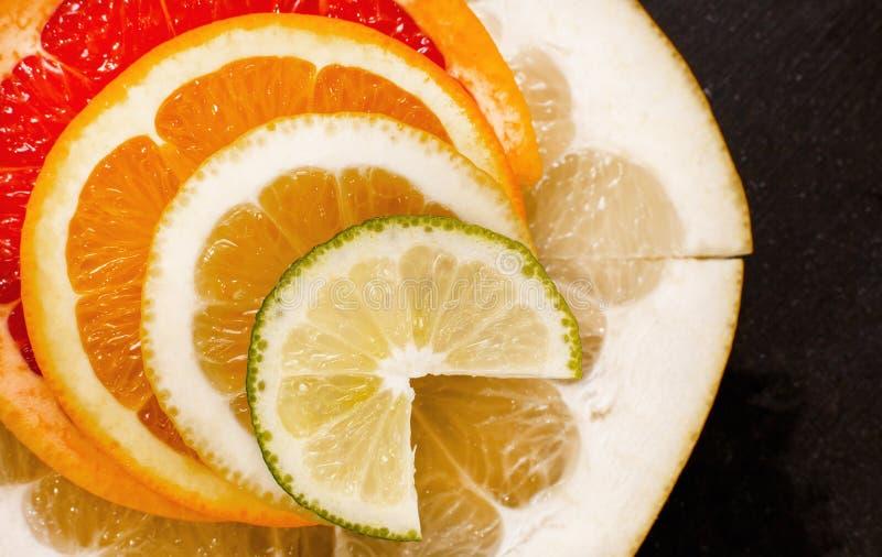 Kreative Zitrusfrüchte schneiden auf einem schwarzen Hintergrund, abstrakt Zitrone, Orange, Kalk, Pampelmuse, Herzchen, Pampelmus stockbilder
