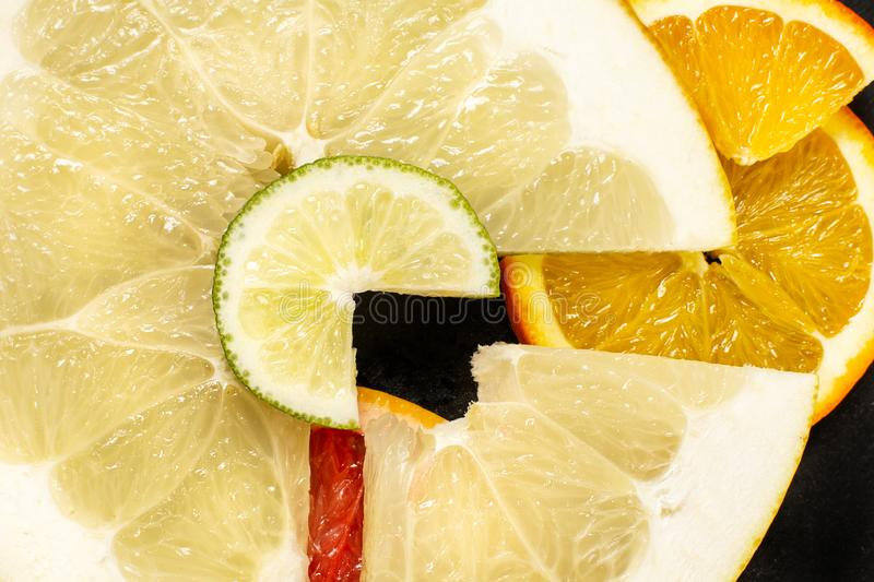 Kreative Zitrusfrüchte schneiden auf einem schwarzen Hintergrund, abstrakt Zitrone, Orange, Kalk, Pampelmuse, Herzchen, Pampelmus stockfotos