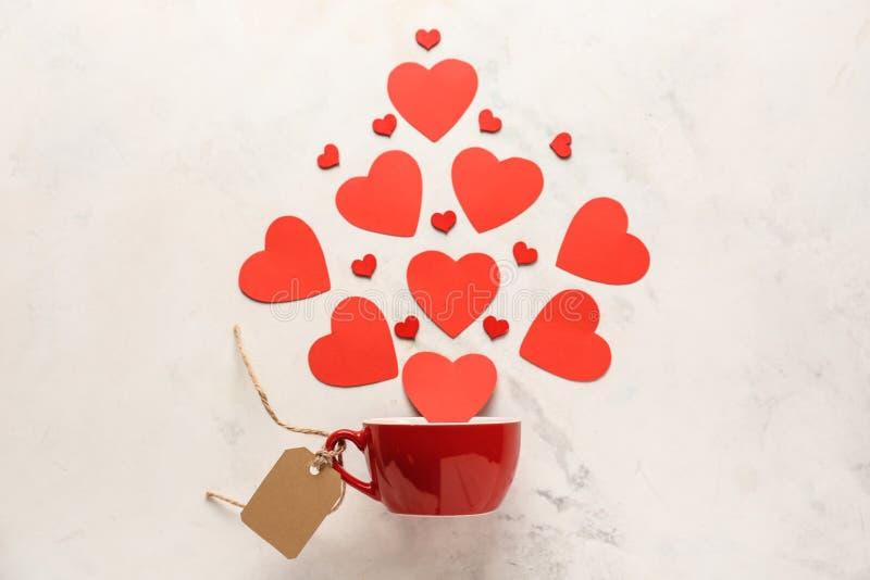 Kreative Zusammensetzung mit den Herzen, die in Schale auf hellem Hintergrund fallen Valentinsgru?-Tagesfeier stockfotos
