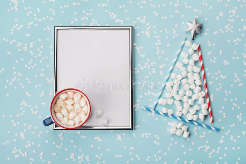 Kreative Zusammensetzung mit heißem Kakao oder Schokolade, silberner Rahmen und Tannenbaum gemacht vom Eibisch auf Winterschreibt stockfoto