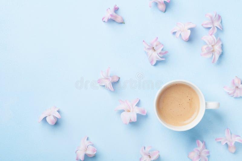 Kreative Zusammensetzung mit Morgenkaffee und rosa Blumen auf Draufsicht des blauen Pastellhintergrundes flache Lageart lizenzfreie stockfotos