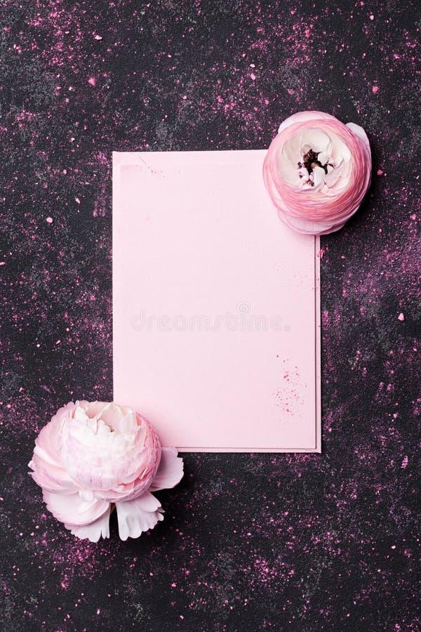 Kreative Zusammensetzung mit rosa leerer und schöner Ranunculuspapierblume auf schwarzer Tischplatteansicht für Heiratsmodelleben stockfoto