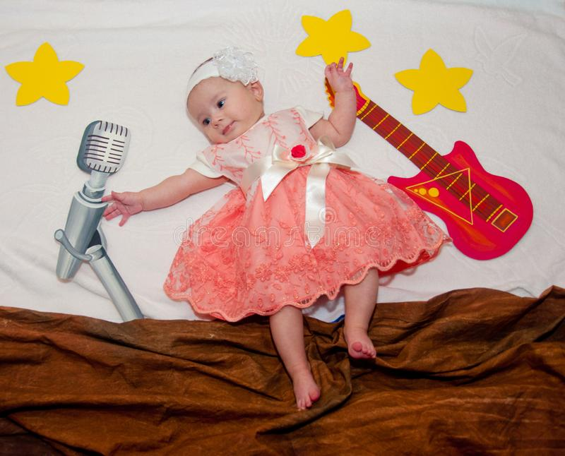 Kreativer Aufbau Kleines Baby, das nahe gezogener Gitarre, Mikrofon und Sternen legt stockbild