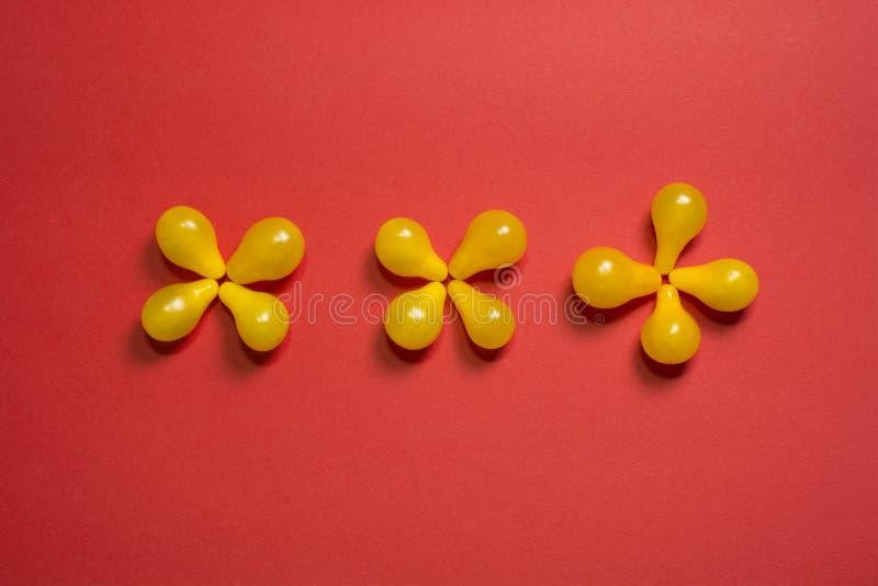 Kreativer Blumenlebensmittelhintergrund Gelbe Kirschtomaten auf Draufsicht des roten Hintergrundes lizenzfreies stockbild
