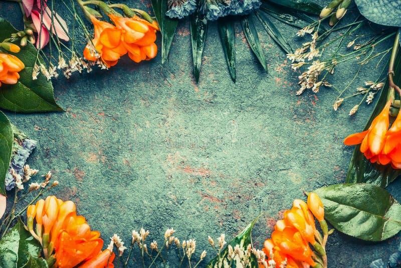 Kreativer Blumenrahmen, der mit tropische Betriebsblumen und -blättern auf dunklem Weinlesehintergrund verfasst lizenzfreie stockfotos