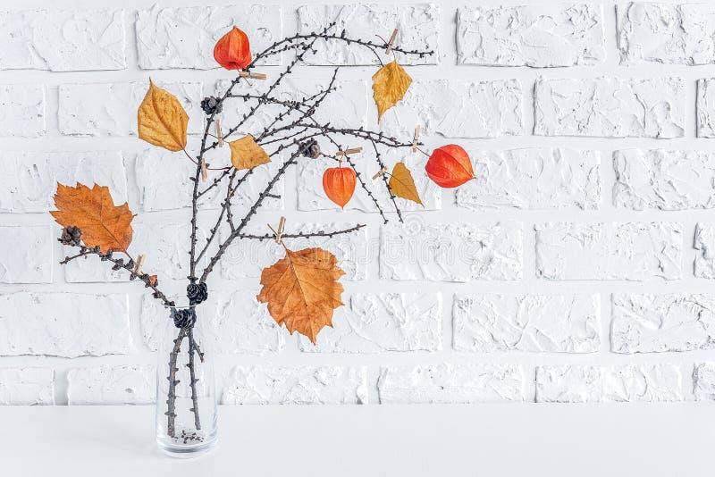 Kreativer Blumenstrauß des Herbstes von Niederlassungen mit gelben Blättern auf Wäscheklammern im Vase auf Kopienraum Backsteinma stockbild