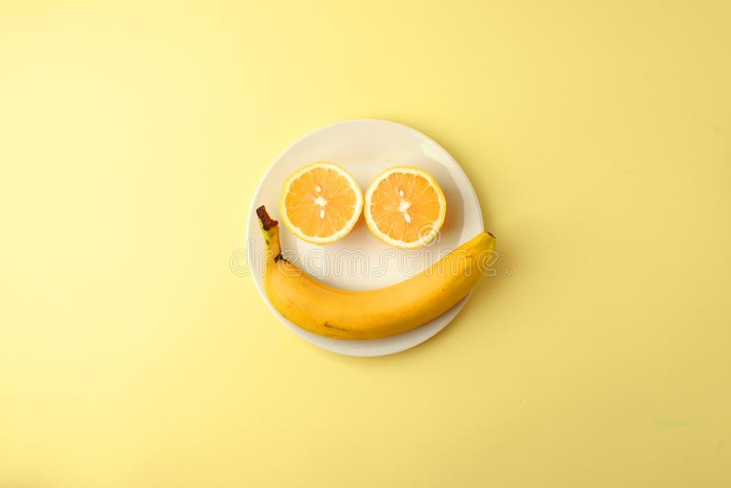 Kreativer einfarbiger Sommerplan gemacht von der Zitrone und von der Banane auf weißer Platte auf gelbem Hintergrund Minimales Ko stockfotografie