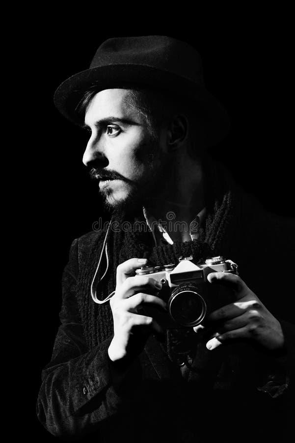 Kreativer Fotograf, der im Studio mit Kamera aufwirft stockfotografie
