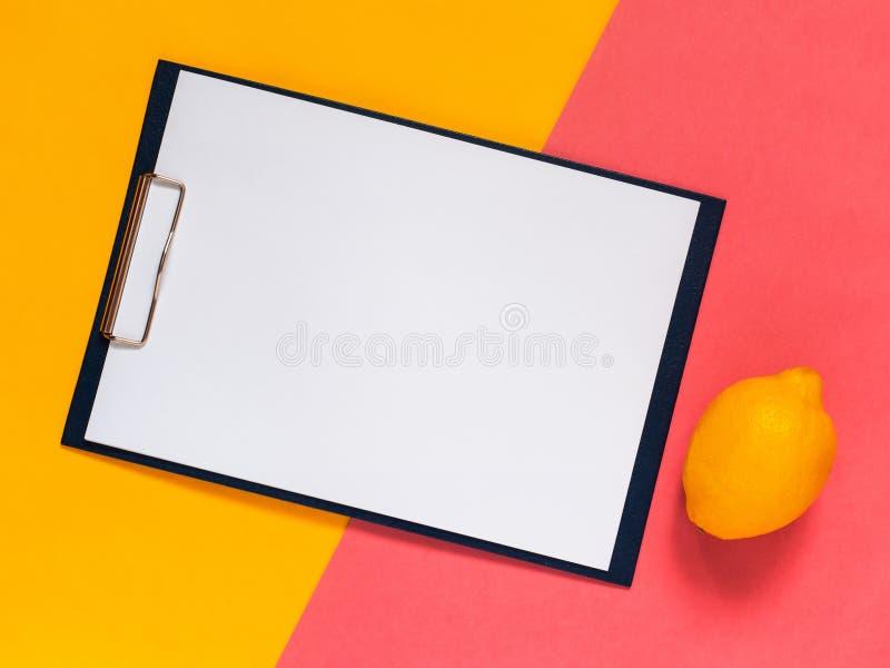 Kreativer geometrischer flacher gelegter Hintergrund Leeres Clipbrett-, Gelbes und rosafarbpapier minimalistic Konzept des Entwur stockfoto