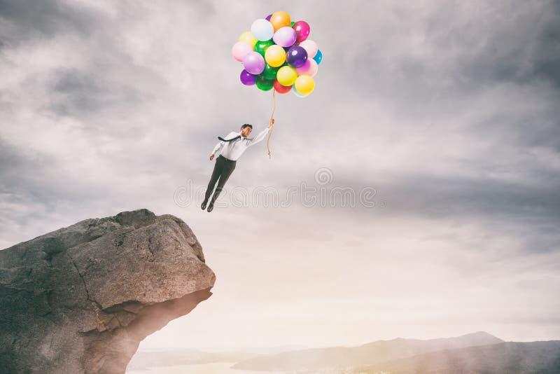Kreativer Geschäftsmann, der bunte Ballonfliegen von der Spitze eines Berges hält stockfotos