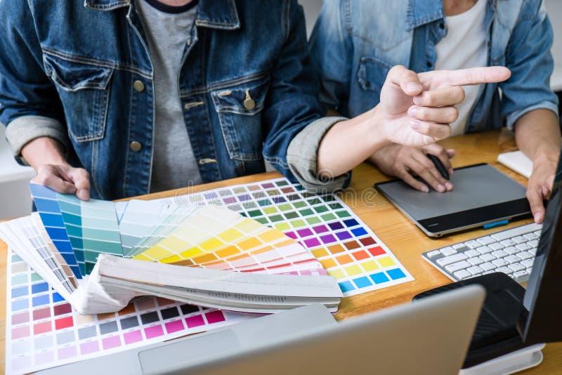 Kreativer Grafikdesigner mit zwei Kollegen, der an Farbauswahl arbeitet und auf Grafiktablette am Arbeitsplatz, Farbmuster zeichn lizenzfreie stockfotografie