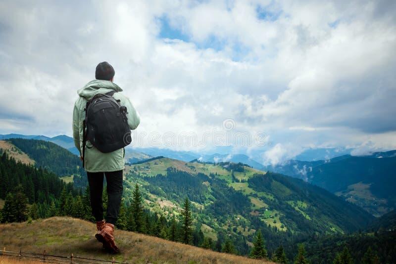 Kreativer Hintergrund, ein Mann ist, ein Mann ist ein Tourist, er geht durch ein Berggebiet mit einem Rucksack riesig Das Konzept lizenzfreies stockfoto