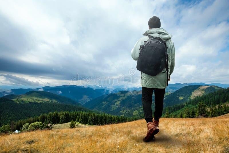Kreativer Hintergrund, ein Mann ist, ein Mann ist ein Tourist, er geht durch ein Berggebiet mit einem Rucksack riesig Das Konzept stockbild