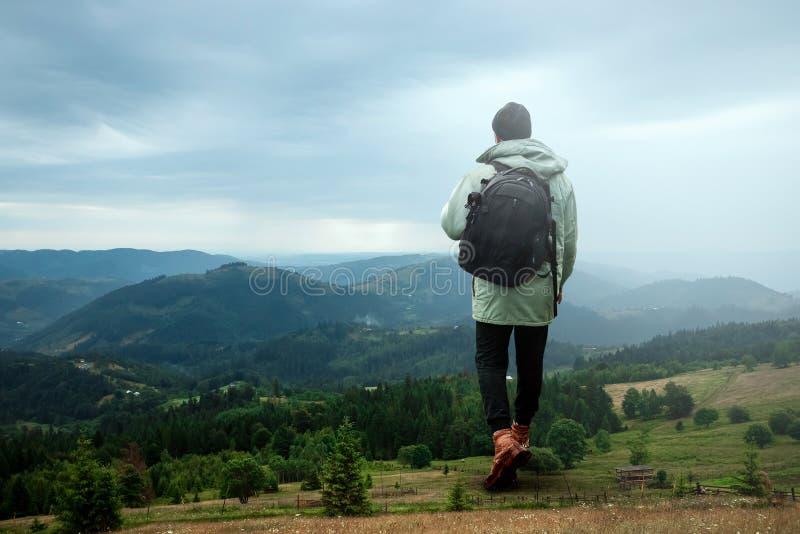 Kreativer Hintergrund, ein Mann ist, ein Mann ist ein Tourist, er geht durch ein Berggebiet mit einem Rucksack riesig Das Konzept lizenzfreies stockbild