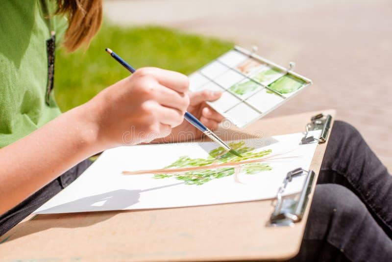 Kreativer Künstler malt ein buntes Bild Nahaufnahme von Händen und von Bürste bei Malerei draußen lizenzfreies stockfoto