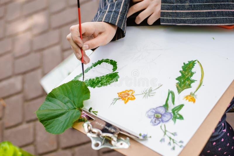 Kreativer Künstler malt ein buntes Bild Nahaufnahme von Händen und von Bürste bei Malerei draußen lizenzfreie stockfotografie