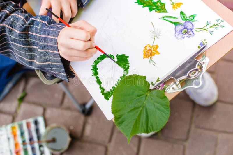 Kreativer Künstler malt ein buntes Bild Nahaufnahme von Händen und von Bürste bei Malerei draußen stockfotografie