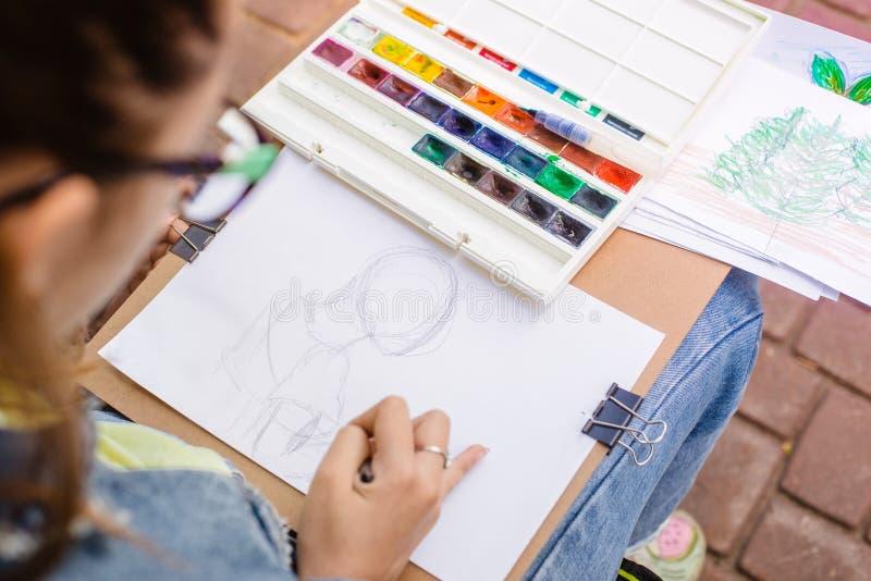 kreativer Künstler malt ein buntes Bild Nahaufnahme von Händen und von Bürste bei Malerei draußen lizenzfreie stockfotos
